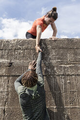Young male free climber at top of sea wall helping friend climb up - CUF07158