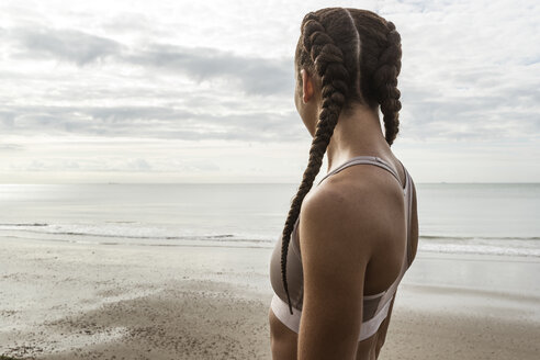 Young female runner with hair plaits looking out to sea from beach - CUF07167