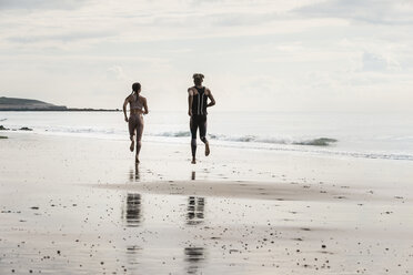 Rear view of young male and female runners running barefoot along beach - CUF07173