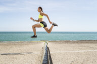 Young woman running outdoors, jumping over gap in bridge, mid air - CUF07179