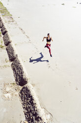 Young woman running along beach, elevated view - CUF07182