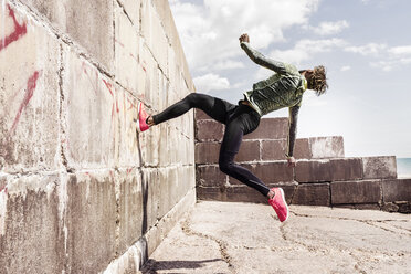Young man, free running, outdoors, running up side of wall - CUF07185