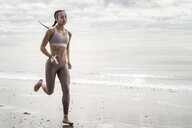 Young woman running along beach - CUF07197