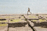 Young woman running along sea wall - CUF07200