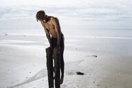 Young man training, doing push ups on wooden beach posts - CUF07215