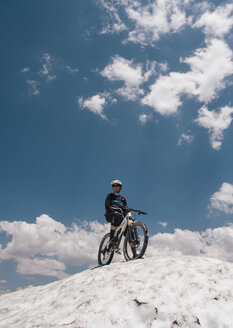 Man with bike on top of snow covered hill, Mammoth Lakes, California, USA, North America - CUF07251