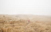 Boy in foggy field landscape, Fairfax, California, USA, North America - CUF07260