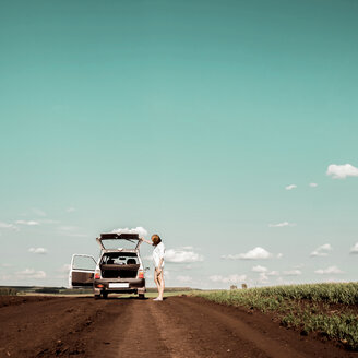 Woman outside car on dirt road, Ural, Sverdlovsk, Russia - CUF07281