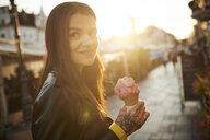 Portrait of young woman holding ice cream, tattoos on hand - CUF07461