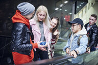 Young adult friends moving up underground station escalator  looking at smartphone - CUF07494