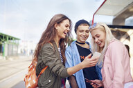 Three young female friends looking at smartphone at city tram station - CUF07509