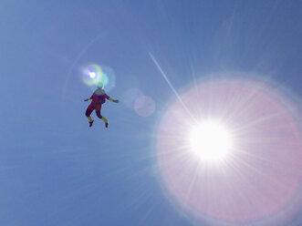 Female skydiver free falling upright against sunlit blue sky - CUF07527