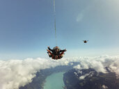 Portrait of tandem skydivers above clouds and landscape - CUF07530