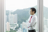 Businessman, arms folded looking out of window - CUF07667