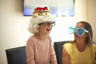 Mother and daughter playing dress up, wearing funny hats and glasses, laughing - CUF07673