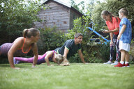 Family exercising in garden, doing push-ups - CUF07694