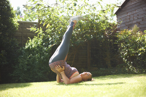 Mature woman exercising in garden, doing shoulder stand - CUF07697