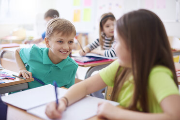 Schoolboy smiling at schoolgirl in class - ABIF00367