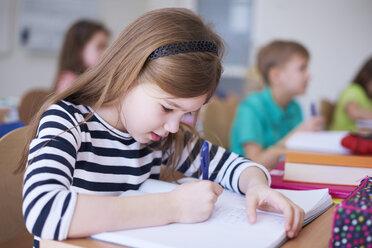Schoolgirl writing in exercise book in class - ABIF00370