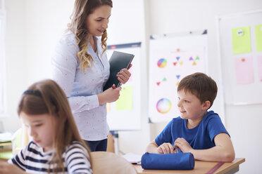 Teacher smiling at schoolboy in class - ABIF00373