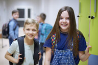 Portrait of smiling schoolboy and schoolgirl at lockers in school - ABIF00376