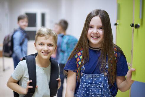 Portrait of smiling schoolboy and schoolgirl at lockers in school - ABIF00376