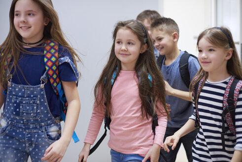 Smiling pupils on corridor leaving school - ABIF00382