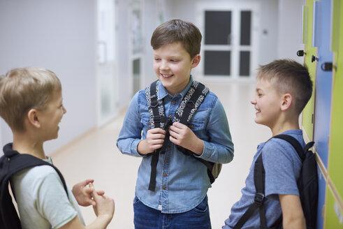 Happy pupils talking at lockers in school - ABIF00385