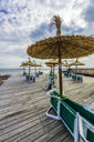 Mallorca, Colonia de Sant Jordi, wooden terrace with straw umbrellas and sun loungers - THAF02160