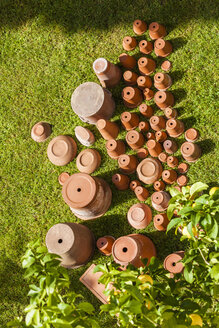 Empty flower pots standing upside down on grass - WDF04657