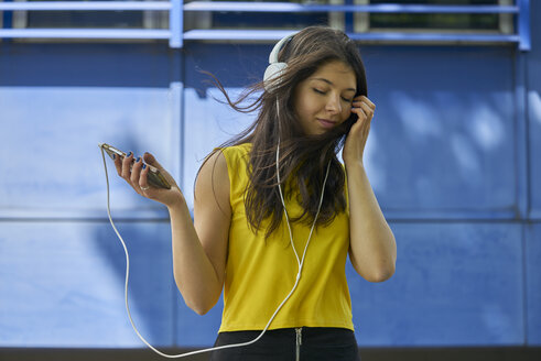 Portrait of young woman listening music with headphones and cell phone - BEF00061