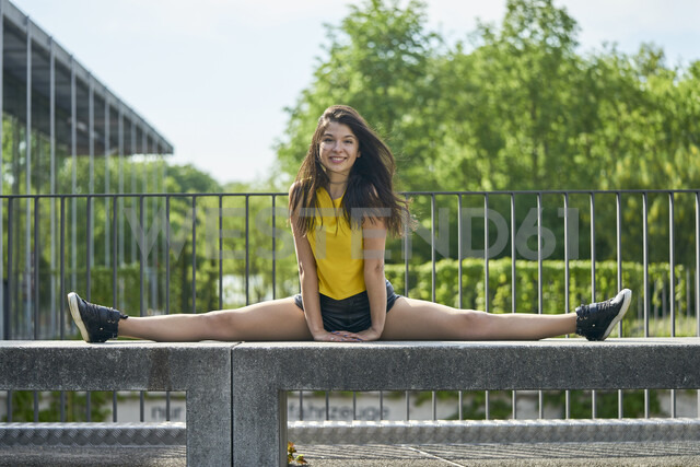 Portrait of smiling young woman doing splits on bench outdoors - BEF00067 - Benjamin Egerland/Westend61