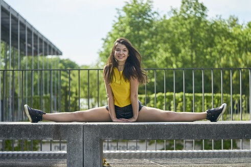 Portrait of smiling young woman doing splits on bench outdoors - BEF00067