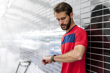 Man having a break from running checking the time on a smartwatch - DIGF04268