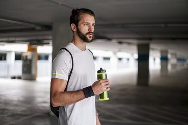 Athlete in parking garage holding drinking bottle - DIGF04280