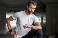 Athlete in parking garage with smartwatch - DIGF04283