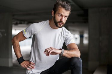 Athlete in parking garage with smartwatch - DIGF04283