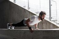 Man doing push-ups on concrete wall - DIGF04286