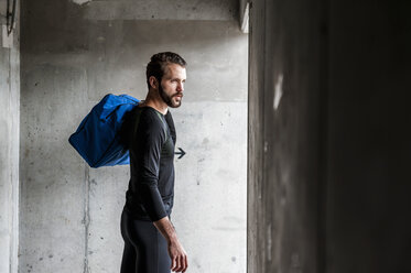 Athlete holding bag at concrete wall - DIGF04292