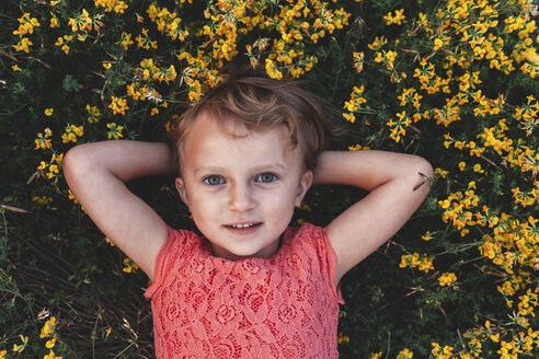 Portrait of girl lying on back amongst yellow wildflowers - ISF01567