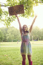 Portrait of young woman holding up free hug sign at festival - ISF01651