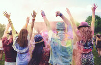 Rear view of young adult friends dancing and throwing coloured chalk powder at festival - ISF01654