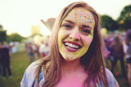 Portrait of young boho woman with face covered in coloured chalk powder at festival - ISF01657