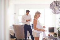 Man looking at smartphone and pregnant girlfriend folding laundry in living room - CUF07799