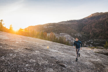 Man running on rock surface at sunset, Yosemite National Park, California, USA - CUF07871