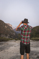 Rear view of man looking through binoculars, Yosemite National Park, California, USA - CUF07874