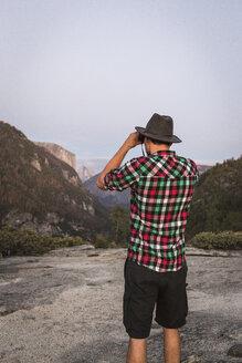 Rear view of man looking through binoculars, Yosemite National Park, California, USA - CUF07874