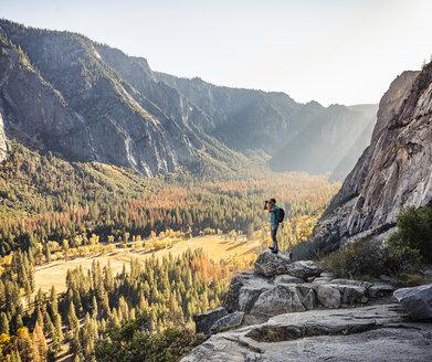 Man on rocky edge looking out through binoculars, Yosemite National Park, California, USA - CUF07877