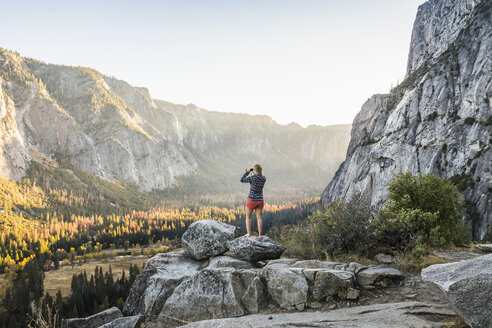 Woman on boulder looking out at valley forest through binoculars, Yosemite National Park, California, USA - CUF07880