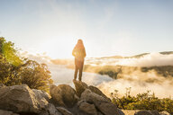 Rear view of woman looking out over valley mist at sunrise, Yosemite National Park, California, USA - CUF07883